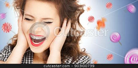 woman with hands on ears stock photo, picture of woman with hands on ears and flying lollipops by Syda Productions