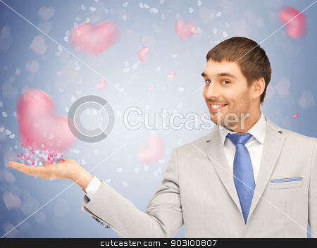 hearts on the palm stock photo, handsome man showing hearts on the palm of his hand by Syda Productions