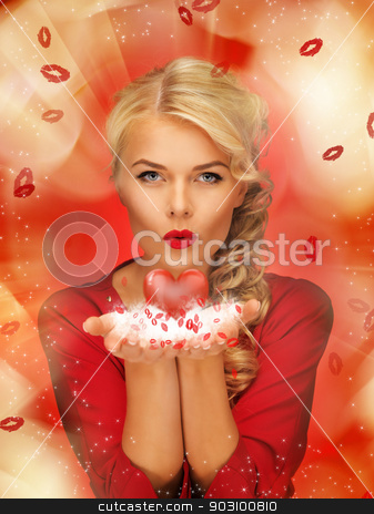 woman blowing kisses on the palms of her hands stock photo, lovely woman in red dress blowing kisses on the palms of her hands by Syda Productions