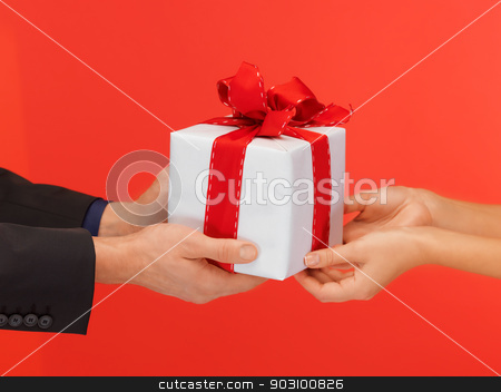 man and woman's hands with gift box stock photo, closeup picture of man and woman's hands with gift box by Syda Productions