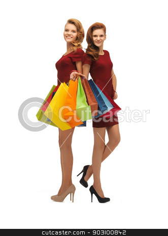 two teenage girls with shopping bags stock photo, picture of two teenage girls in red dresses with shopping bags by Syda Productions