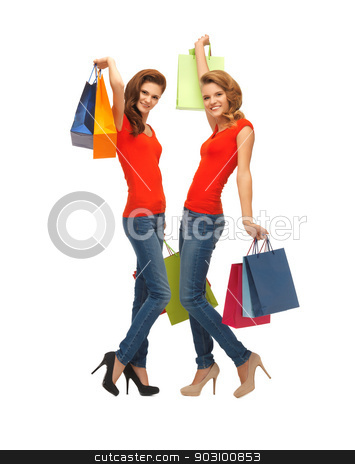 two teenage girls with shopping bags stock photo, two teenage girls in red t-shirts with shopping bags by Syda Productions