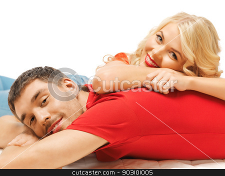 happy couple lying at home stock photo, bright picture of happy couple lying at home (focus on man) by Syda Productions