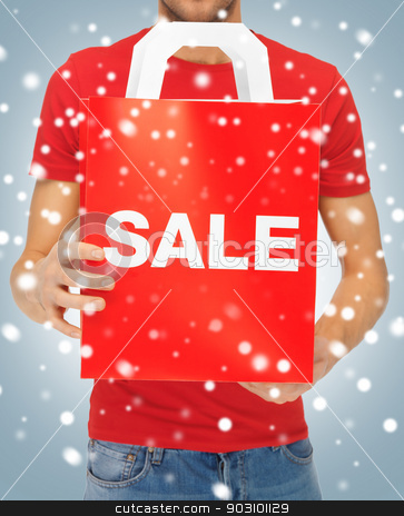 man's hands holding shopping bag stock photo, closeup picture of man's hands holding shopping bag by Syda Productions