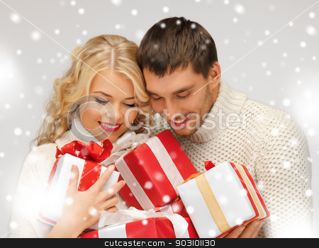 romantic couple in a sweaters with gift boxes stock photo, picture of romantic couple in a sweaters with gift boxes by Syda Productions