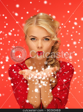 woman blowing snow on the palms of her hands stock photo, lovely woman in red dress blowing snow on the palms of her hands by Syda Productions