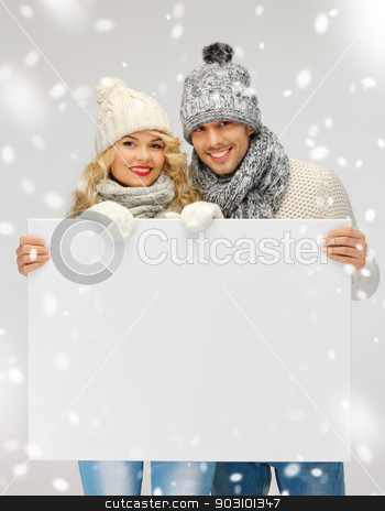 couple in a winter clothes holding blank board stock photo, picture of family couple in a winter clothes holding blank board by Syda Productions