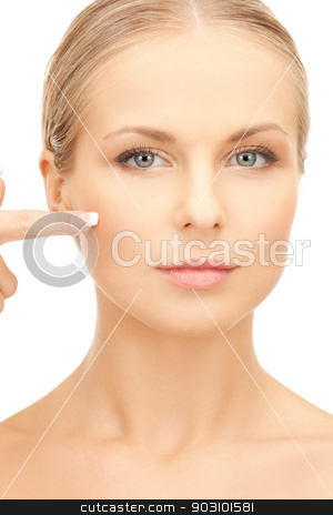 beautiful woman pointing to cheek stock photo, bright picture of beautiful woman pointing to cheek. by Syda Productions