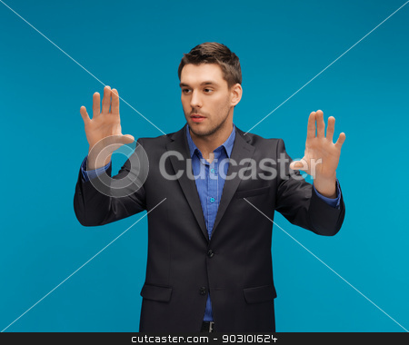 man in suit working with something imaginary stock photo, picture of man in suit working with something imaginary. by Syda Productions