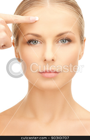 beautiful woman pointing to forehead stock photo, picture of beautiful woman pointing to forehead by Syda Productions