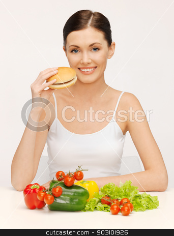 woman with hamburger and vegetables stock photo, picture of beautiful woman with hamburger and vegetables by Syda Productions