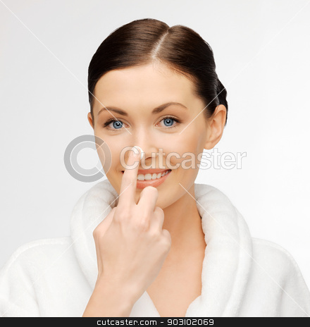 woman in bathrobe applying creme stock photo, picture of beautiful woman in bathrobe applying creme by Syda Productions