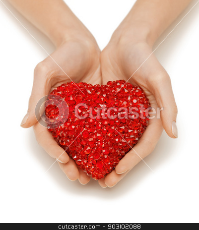 woman hands holding heart stock photo, bright closeup picture of woman hands holding heart by Syda Productions