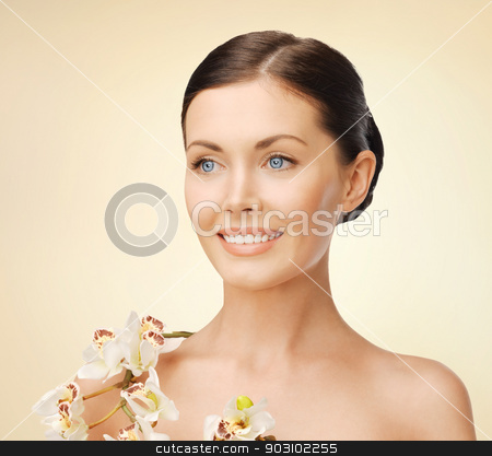 lovely woman with orchid flower stock photo, bright picture of lovely woman with orchid flower by Syda Productions