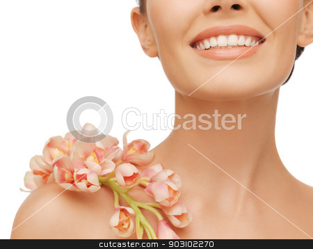 smiling woman with orchid flower on her shoulder stock photo, closeup picture of smiling woman with orchid flower on her shoulder by Syda Productions
