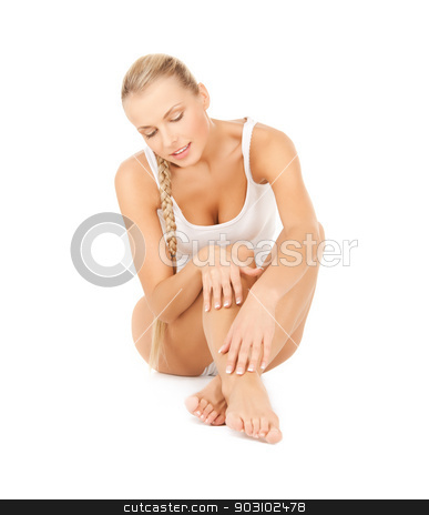 beautiful woman touching her legs stock photo, picture of beautiful woman in cotton underwear touching her legs by Syda Productions