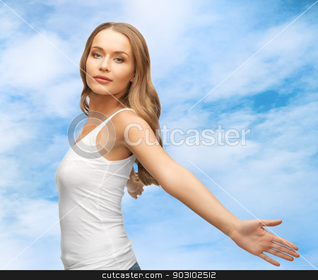 woman spreading hands stock photo, picture of happy woman spreading hands over blue sky. by Syda Productions