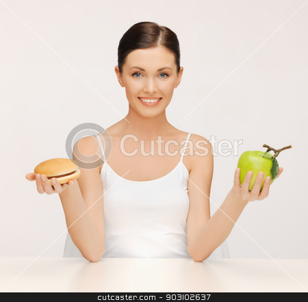 woman with hamburger and apple stock photo, picture of beautiful woman with hamburger and apple by Syda Productions