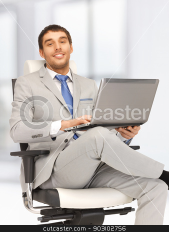 young businessman sitting in chair with laptop stock photo, picture of young businessman sitting in chair with laptop by Syda Productions