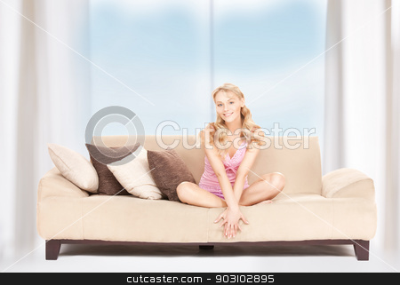 happy woman on sofa stock photo, bright picture of happy woman on sofa by Syda Productions