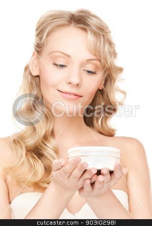 woman in bathrobe stock photo, picture of woman in bathrobe applying cream by Syda Productions