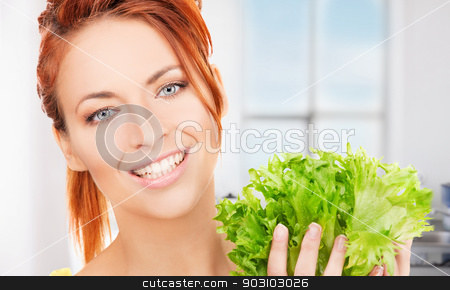 happy woman with lettuce stock photo, picture of happy woman with lettuce in the kitchen by Syda Productions