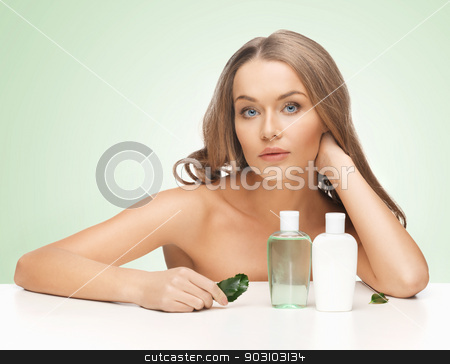 woman with cosmetic bottles stock photo, picture of woman with cosmetic bottles and leaf by Syda Productions
