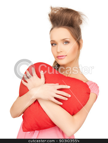 happy and smiling woman with heart-shaped pillow stock photo, picture of happy and smiling woman with heart-shaped pillow by Syda Productions