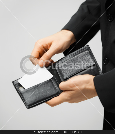 man in suit holding credit card stock photo, man in suit with wallet and credit card. by Syda Productions