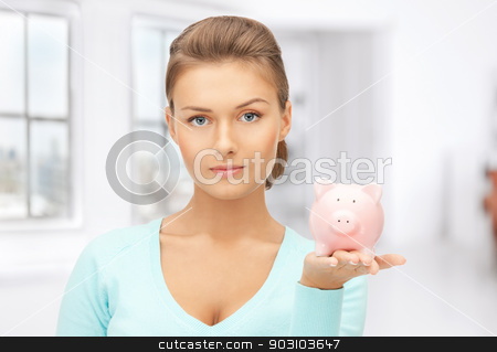 lovely woman with piggy bank stock photo, picture of lovely woman with piggy bank by Syda Productions