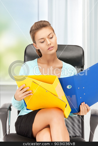 young businesswoman with folders sitting in chair stock photo, picture of young businesswoman with folders sitting in chair by Syda Productions