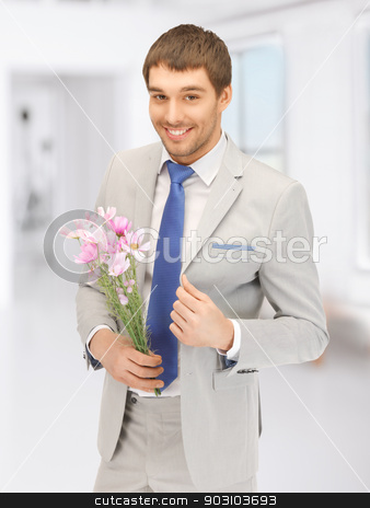 handsome man with flowers in hand stock photo, picture of handsome man with flowers in hand by Syda Productions