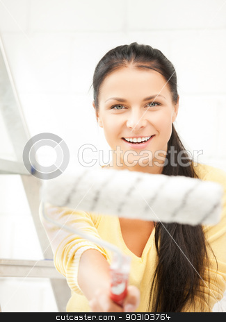 happy young woman with paintroller stock photo, picture of happy young woman with paintroller by Syda Productions
