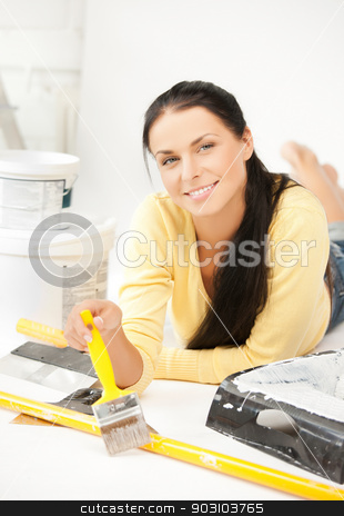 woman with paintbrush and renovating tools stock photo, happy young woman with paintbrush and renovating tools by Syda Productions