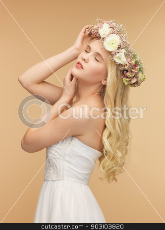 woman wearing wreath of flowers stock photo, picture of young woman wearing wreath of flowers by Syda Productions
