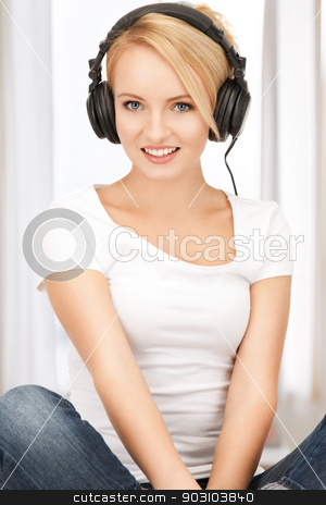 happy teenage girl in big headphones stock photo, picture of happy teenage girl in big headphones by Syda Productions
