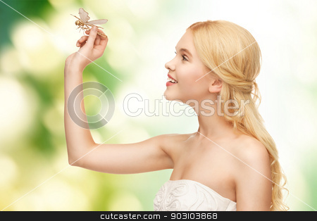 woman with dragonfly in hand stock photo, picture of beautiful woman with dragonfly in hand by Syda Productions