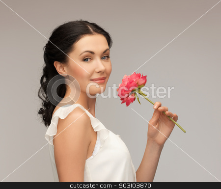 smiling woman smelling flower stock photo, picture of smiling young woman smelling flower by Syda Productions