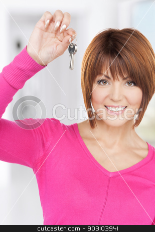 happy woman with keys stock photo, picture of happy woman with keys at home by Syda Productions