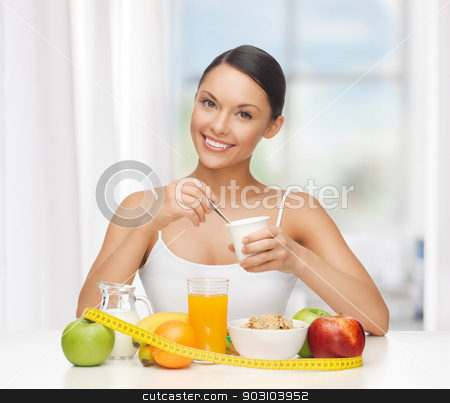 woman with healthy breakfast and measuring tape stock photo, young woman with healthy breakfast and measuring tape by Syda Productions