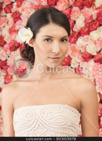 woman with background full of roses stock photo, beautiful woman with background full of roses by Syda Productions