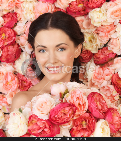 woman with background full of roses stock photo, portrait of beautiful woman with background full of roses by Syda Productions