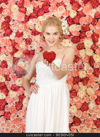 woman with heart and background full of roses stock photo, young woman with heart and background full of roses by Syda Productions
