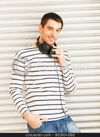 handsome man with headphones stock photo, man in casual clothes with headphones leaning to wall by Syda Productions