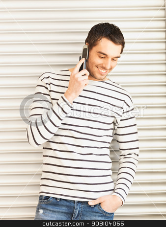 man in casual clothes talking on the phone stock photo, handsome man in casual clothes talking on the phone by Syda Productions