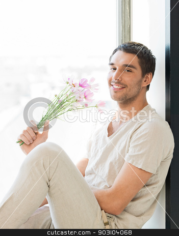 man holding bouquet of flowers stock photo, man sitting on the windowsill holding bouquet of flowers... by Syda Productions