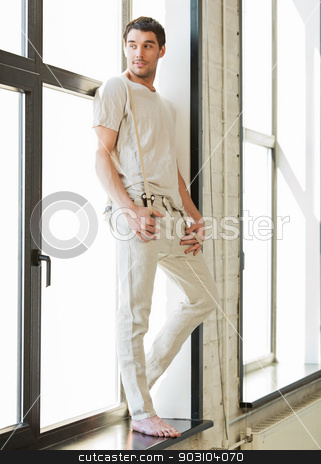 handsome man standing on the windowsill stock photo, portrait of handsome man standing on the windowsill by Syda Productions