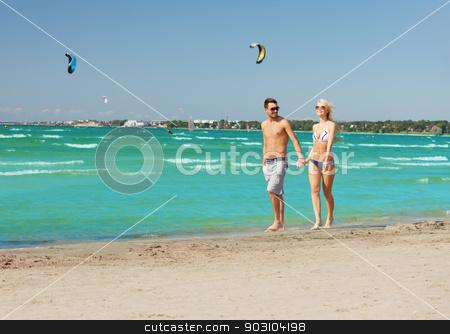 couple walking on the beach stock photo, picture of happy couple walking on the beach. by Syda Productions