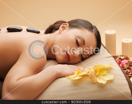 beautiful woman with hot stones stock photo, picture of woman in spa salon with hot stones by Syda Productions