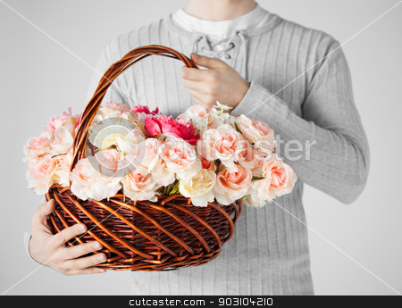 man holding basket full of flowers stock photo, close up of man holding basket full of flowers. by Syda Productions